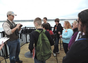 Onondaga Audubon Society Board Member Frank Moses shows students how to use binoculars.