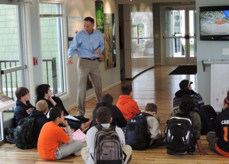 Honeywell Syracuse Program Director John McAuliffe answers students' questions about lake restoration activities after they view a video about the lake cleanup process.