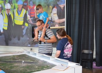 Kevin, Amber, and Eli Geidel of Liverpool, New York, view the Onondaga Lake watershed map at Honeywell's exhibit.