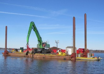 Cap material consisting of larger rocks is applied by equipment mounted on a barge.