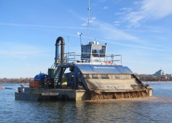 A specialized barge applies cap material consisting primarily of sand to the lake bottom.