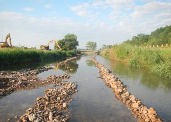 A temporary access road is built into the creek to allow excavators to access both sides of the stream.