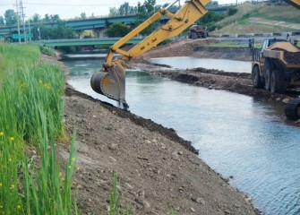 An excavator places topsoil along the shoreline. A seed mix of native plant species will be spread along the shoreline to prevent erosion and create habitat.