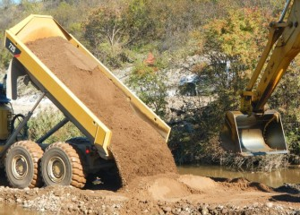 Sand is delivered and placed in Nine Mile Creek with an excavator to create a new creek bottom.
