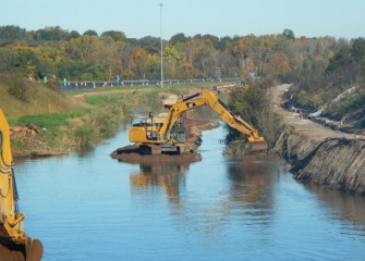 Crews use excavators in the middle of Nine Mile Creek to access both banks. I-690 can be seen in the background.