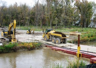 A temporary floating bridge is built across Nine Mile Creek to allow work crews to access a forested wetland.