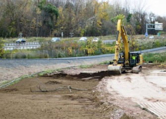 Topsoil is placed over the clay-like soil. The county's western shoreline trail, under construction, is immediately to the left; I-690 is in the background.