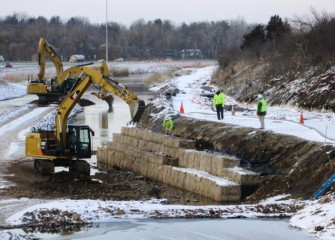 Work on a retaining wall continues in winter, taking advantage of the low flow period in the creek. Later when shrubs and trees are added, the wall will take on the appearance of a natural shoreline.