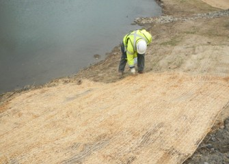 A worker places fresh erosion control blanket made of natural fibers along the banks.