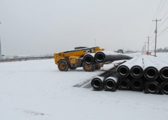 New sections of double-walled pipe, manufactured locally, are stockpiled before welding.