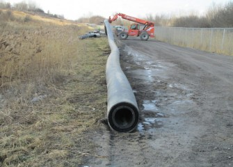 A new section of pipeline is moved into place. The pipeline will be tested with water before lake material is transported through it.