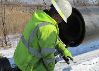 A worker welds spacer rings between the 16-inch and 22-inch pipes.