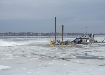 In late March, the largest dredge is pushed out into the lake to help clear ice in the work area.