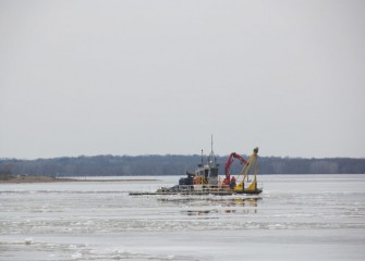 A support boat moves out into the ice-covered lake in preparation for the start of lake activities.