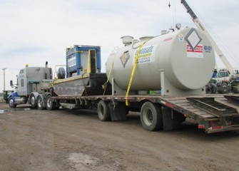 A boat to assist in lake operations and a tank to store biodiesel fuel arrive on a flatbed trailer.