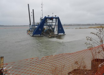 A dredge removes lake bottom material near the barrier wall (lower right corner).  Plans are to complete dredging in 2014, a year ahead of schedule.