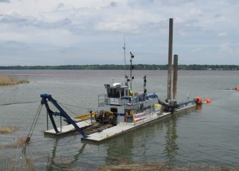 The medium-sized dredge works near the mouth of Nine Mile Creek.