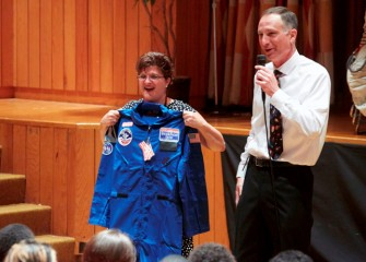 Linda Trippany is presented her flight suit by Honeywell Syracuse Program Director John McAuliffe. Trippany will use the suit at Honeywell Educators @ Space Academy during simulated astronaut training.