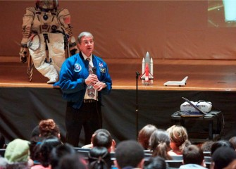 "The ""astronaut"" seated on stage is an actual space suit Dr. Thomas brought to show students."