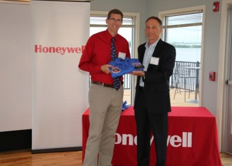 Math teacher Christopher Ludden, C.W. Baker High School in Baldwinsville, receives his flight suit from Honeywell Syracuse Program Director John McAuliffe.