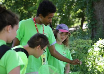 Marcel Young-Scaggs points out identifying characteristics of a plant.  Rebecca Rolnick (right), a 2011 participant in Honeywell Summer Science Week at the MOST and volunteer this year, looks on.