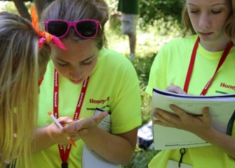 Karsyn Plis (left), from Camillus Middle School, and Katie Eno, from West Genesee Middle School, describe an aquatic insect found in Onondaga Creek while Hannah Walsh, also from West Genesee Middle School, records observations in her handbook.