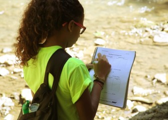 Student Bianca Melendez Martineau from Manlius Pebble Hill School records stream velocity measurements in her workbook.