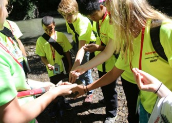 Students feel soil from the creek shoreline to assess moisture, consistency, and other characteristics.