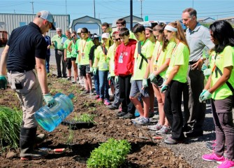 Tony Eallonardo (left), scientist at O'Brien & Gere, demonstrates how to water new plantings.  Honeywell Syracuse Program Director John McAuliffe (right) listens along with students.