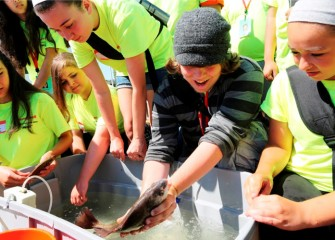 Luke Burgess, from Expeditionary Learning Middle School in Syracuse, holds a freshwater drum, also called sheepshead.