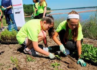 Abigail Zumbuhl (left), from Jamesville-DeWitt Middle School, plants black-eyed Susan together with Anna Markert, from Pine Grove Middle School in East Syracuse.