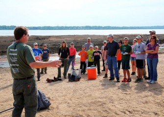 Steve Mooney, managing scientist at O'Brien & Gere and Corps volunteer, briefs a group of attendees before they begin planting along the Onondaga Lake shoreline.