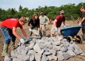 Natalia Cagide-Elmer (center), environmental engineer at Parsons, works with other Corps volunteers to build a rock pile to support reptiles and small mammals. Smaller animals in turn serve as food sources for larger animals and birds.