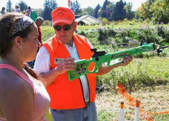 Sportsmen Education Instructor Dick Culkin teaches Kaylee Gadoua from Syracuse how to hold a crossbow.