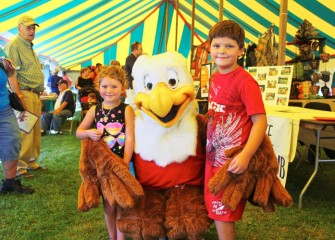 "Teagan (left) and Mason Wojieck, from Red Creek, pose with ""Eddie the Eagle,"" National Rifle Association's safety program mascot, in one of the display tents."