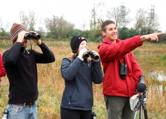 Brian Cocca (left) and Liverpool Middle School math teacher Sara Pieklik (center) spot birds.  In total, 28 species were observed during the 3-hour event.