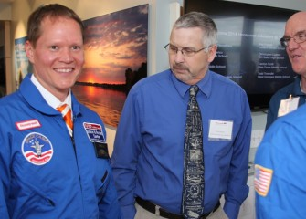 Central New York Space Academy alumni Brian Ramsden (2013, center) and Dan Howard (2012, right) admire West Genesee Middle School teacher Todd Troendle's new flight suit.