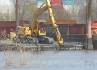 An excavator with a rake attachment is used to lift old tires out of the lake.