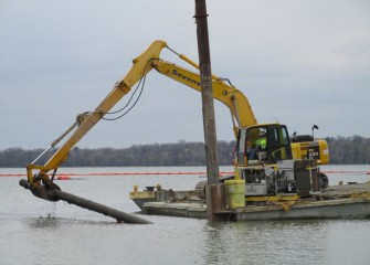 An old cast iron pipe is removed from the lake.
