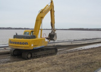 Pipe used in capping operations is lined along the shore before placing in the lake.