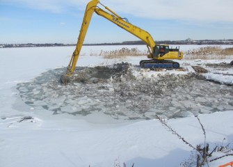 Ice must be cleared with an excavator as work continues rebuilding the southwest shoreline.