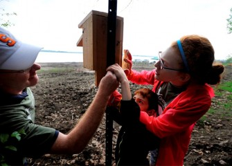 Abby Bustin (right) works on fastening a nest box to a pole with her brother Nathan and father Cary.