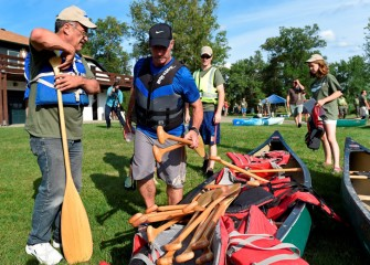 Volunteers collect equipment near the Syracuse Chargers Boathouse.