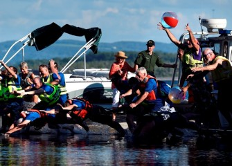 Community members and elected and appointed officials jump and dive into the lake.