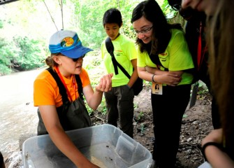 Lead Counselor Renee Halloran and students observe aquatic insects found in Onondaga Creek.