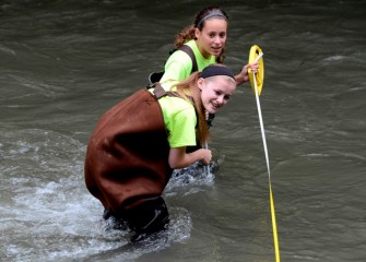 Sidney Chafee (foreground), from Solvay Middle School, and Madison Vanelli, from West Genesee Middle School, measure water velocity in a fast-moving Onondaga Creek.