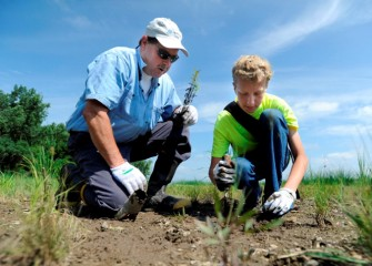 Steve Mooney, Managing Scientist at O'Brien & Gere and Onondaga Lake Conservation Corps volunteer, helps Evan Blust from Jamesville-Dewitt Middle School plant native species along the Onondaga Lake shoreline.
