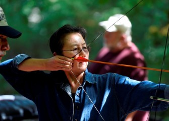Attendees not only observe, but also have the chance to try out various activities with coaching by skilled practitioners.  Mimi Mark, from Tully, tries archery.