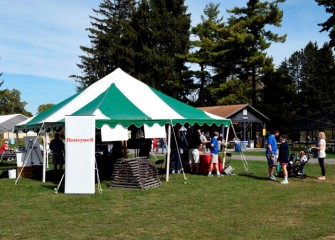 People stop at the Honeywell hospitality tent to visit various exhibits and learn about continuing progress on the habitat restoration part of the Onondaga Lake cleanup.