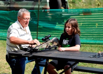Josh O'Connor (right), from Syracuse, learns how a crossbow works from Lance Robson of the Falcon Sportsmen Club in Auburn.  Robson is also Chair of the New York State Fish and Wildlife Management Board.